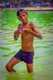 德里,印度- 2017年9月16日:而他是里面,关闭看照相机的未认出的微笑的印地安男孩 库存照片