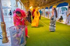 德里,印度- 2017年9月19日:走在一张绿色地毯的广场的未认出的人民,有妇女储蓄的 免版税库存图片