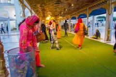 德里,印度- 2017年9月19日:走在一张绿色地毯的广场的未认出的人民,有妇女储蓄的 免版税图库摄影