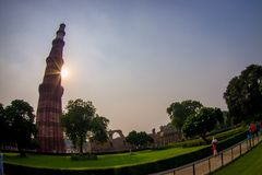德里,印度- 2017年9月25日:走近在日落的Qutub Minar,最高独立的未认出的人民 库存图片