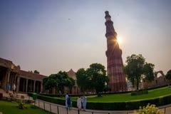 德里,印度- 2017年9月25日:走近在日落的Qutub Minar,最高独立的未认出的人民 免版税库存照片
