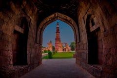 德里,印度- 2017年9月25日:Qutub Minar美丽的景色,通过扔石头的曲拱,一个联合国科教文组织世界heritag 免版税库存照片