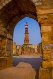 德里,印度- 2017年9月25日:Qutub Minar美丽的景色,通过扔石头的曲拱,一个联合国科教文组织世界heritag 免版税图库摄影