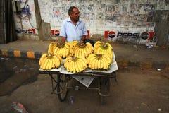 德里6月09日:卖在街道上的老人banans在德里 免版税图库摄影