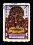 徽章和产业场面,苏联的第50周年,大约1972年 免版税库存照片
