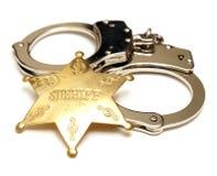 徽章把县司法行政官扣上手铐 免版税库存图片