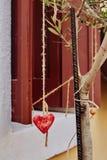 心形下垂垂悬在一个树枝作为爱的标志 免版税库存图片