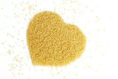 心形从甘蔗顶视图的糖,黄褐色背景的砂糖,蔗糖糖,红色糖 免版税图库摄影