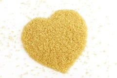 心形从甘蔗顶视图的糖,黄褐色背景的砂糖,蔗糖糖,红色糖 免版税库存图片