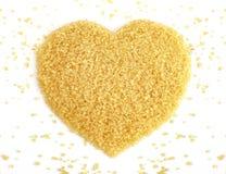 心形从甘蔗顶视图的糖,黄褐色背景的砂糖,蔗糖糖,红色糖 库存照片