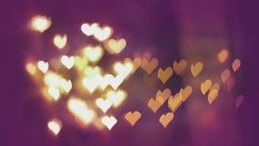 心形浪漫华伦泰` s的天上色了在紫罗兰色背景的bokeh光 股票录像