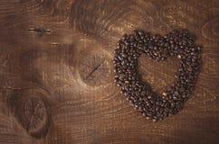 心形由咖啡豆做了在黑暗的木背景 库存照片