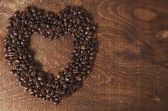 心形由咖啡豆做了在黑暗的木背景 库存图片