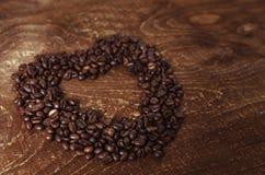心形由咖啡豆做了在黑暗的木背景 免版税图库摄影