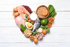 心形由自然食物制成高在蛋白质在白色木背景 免版税图库摄影