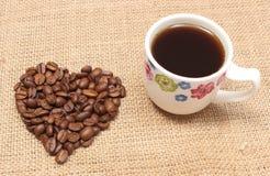 心形的咖啡豆和杯子无奶咖啡 免版税库存图片