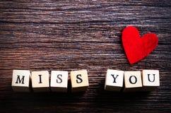 心形的嚼的糖果和词想念您立方体的,木背景 您的文本的空位 图库摄影