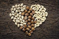 心形的坚果:榛子、开心果和腰果 免版税库存图片