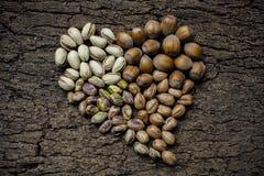 心形的坚果:榛子和开心果 免版税库存图片