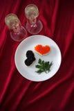 心形的多士用红色和黑鱼子酱和两杯在白色板材的香槟在红色布 免版税图库摄影
