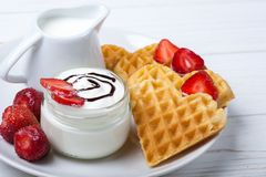 心形的奶蛋烘饼用草莓,奶油沙司、投手用牛奶在白色板材和白色背景 免版税图库摄影