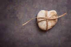心形的岩石小卵石栓与在深蓝紫色石背景,概念性,关系,华伦泰,婚姻的麻线 图库摄影