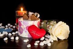 心形的巧克力爱与蜡烛和白色玫瑰情人节 免版税图库摄影