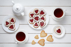心形的曲奇饼为与茶壶和两杯茶的情人节在白色木背景的 库存照片