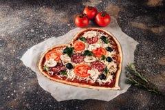 心形的未加工的薄饼用蕃茄和无盐干酪为在葡萄酒混凝土背景的情人节 食物概念  免版税库存照片
