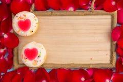 心形的杯形蛋糕和红色玫瑰与木板 免版税库存图片