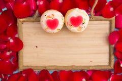 心形的杯形蛋糕和红色玫瑰与木板 免版税图库摄影