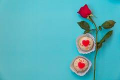心形的杯形蛋糕和红色玫瑰 免版税库存照片