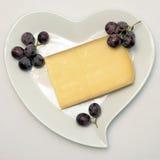 心形的板材用法国乳酪和葡萄 免版税库存照片