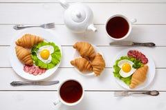 心形的煎蛋、沙拉、新月形面包、蒜味咸腊肠香肠、构成和茶在白色木桌背景 免版税库存照片