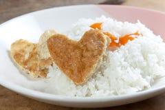 心形的煎蛋卷和米在白色盘 免版税库存照片
