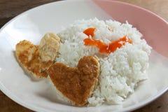 心形的煎蛋卷和米在白色盘 库存照片