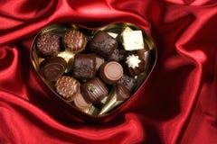 心形的箱在红色缎背景的糖果 免版税库存照片