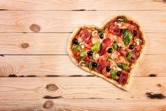 心形的薄饼用蕃茄和熏火腿为在葡萄酒木背景的情人节 食物概念  免版税库存照片