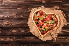 心形的薄饼用蕃茄和熏火腿为在葡萄酒木背景的情人节 食物概念  免版税库存图片