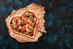 心形的薄饼用蕃茄和熏火腿为在葡萄酒的情人节染黑绿松石背景 在倾吐的餐馆沙拉的主厨概念食物新鲜的厨房油橄榄 免版税库存照片