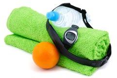 心率显示器、瓶水,桔子和毛巾 免版税库存照片