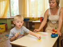 心理学家和一个孩子有唐氏综合症的执行 免版税图库摄影