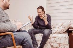 心理学家咨询和心理疗期概念 谈论他的问题的被注重的人 库存图片