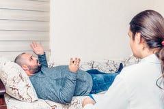 心理学家咨询的会议 供以人员说谎在沙发,抱怨他的问题 免版税图库摄影