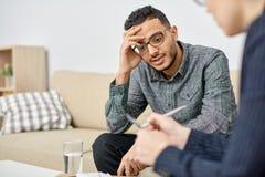 心理学家咨询的沮丧的患者 免版税库存照片