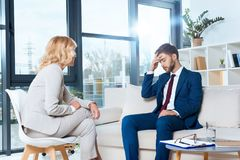 心理学家谈话与沮丧的年轻患者 库存照片