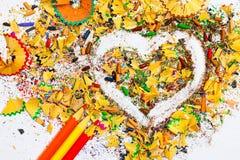 心脏、三支铅笔和色的木削片 免版税库存照片