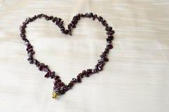 心脏为华伦泰` s天由女性美丽的小珠,棕色黑暗的石头项链做成,琥珀色反对背景米黄很好 库存照片