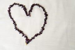 心脏为华伦泰` s天由女性美丽的小珠,棕色黑暗的石头项链做成,琥珀色反对背景米黄很好 图库摄影