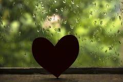 心脏剪影在老木窗口和雨下落背景的 免版税图库摄影